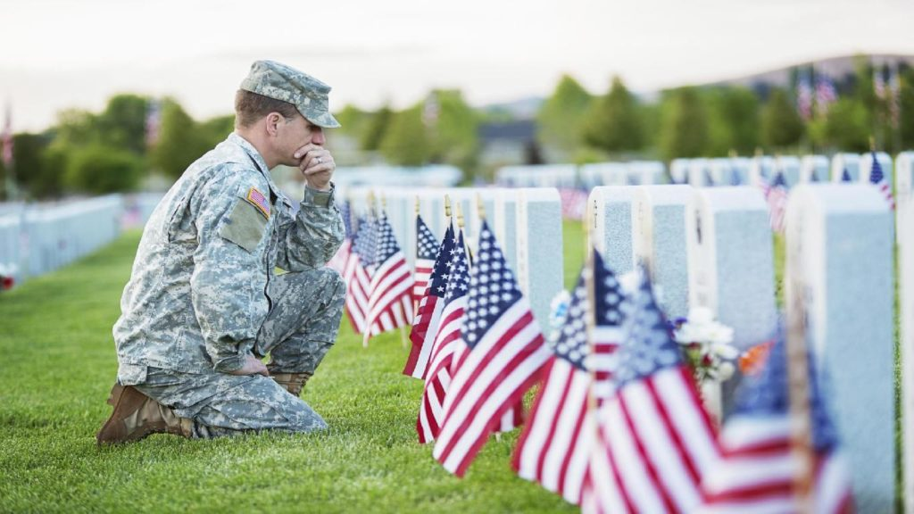 Uniformed U.S. Soldier Kneeling at Grave to Honor Fallen Heroes for Fourth of July